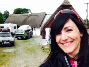 meg in front of thatched cottage